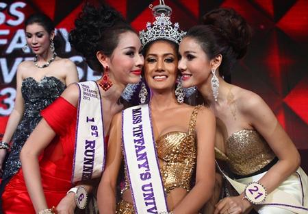 Miss Tiffany's Universe 2013 Netnapada 'Neck' Kalyanon (center) receives a congratulatory peck on the cheek from first runner up Chananchida 'Blossom' Rungpetcharat (left) and second runner up Sopida 'Ning' Rachanon (right).