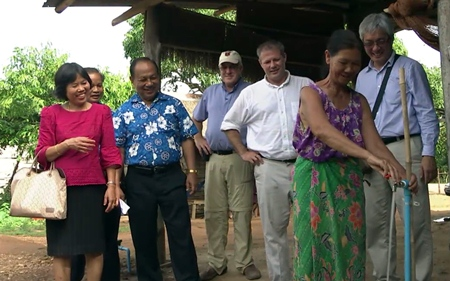 An overjoyed villager turns on the tap for the first time, much to the delight of Rotarians from both countries.