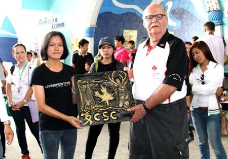 Nong (center) presents a plaque of appreciation she made to Wayne Ogonoski representing the Canadian Jackalope Open.