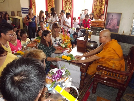 Buddhists present Sanghathan and other items to monks at Wat Chaiyamongkol.