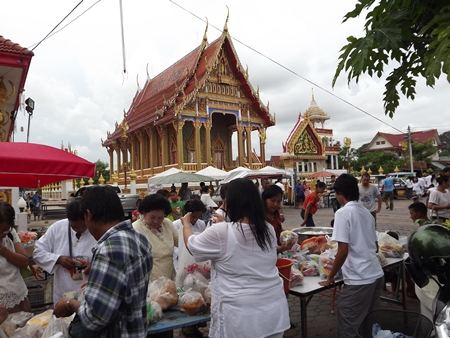 At Wat Nongyai, citizens purchase food to present as alms.