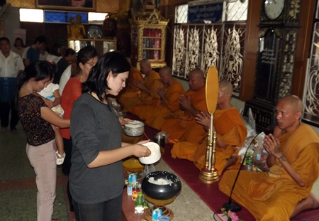 Faithful Buddhists offer alms and make merit on Visakha Bucha Day at Wat Nongyai.