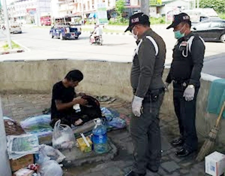 Municipal police officers question this person, and finding him to be homeless, transfer him to a shelter.