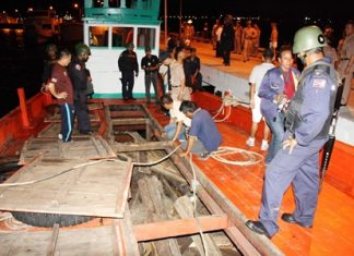 Officials inspect the smuggled rosewood found in the fish holds of this Cambodian fishing boat.