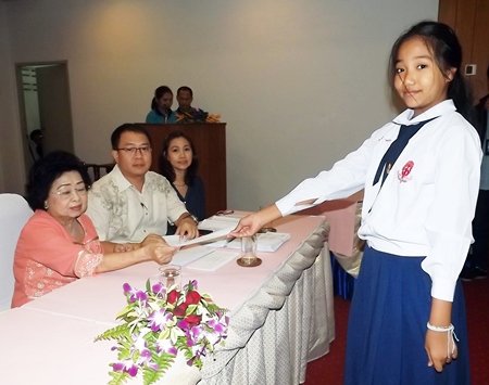 Mrs. Wanthanee Supornsahatrangsi (left), assistant MD of Sunshine hotels and resorts, presents 2,000 baht scholarships to children in Prathom 1-6.