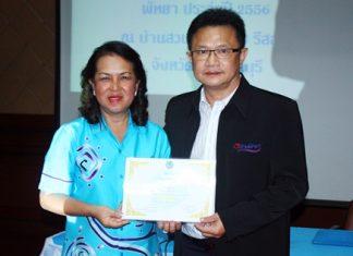 Deputy Mayor Wutisak Rermkitkarn presents a certificate to Ms. Naowarat Khakhay, president of the Pattaya Women's Development Group.