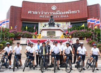 Deputy Mayor Ronakit Ekasingh (center left), and Pol. Lt. Col. Arun Promphan (center right) pose for a group photo with patrol officers and municipal officers after the new bicycle handover.