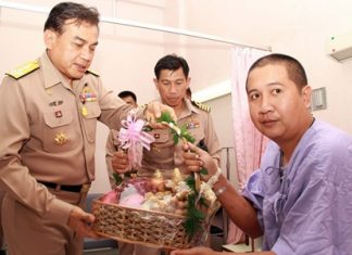 Royal Thai Navy commander Adm. Surasak Runroengrom presents a gift basket to Petty Officer First-Class Sayan Inbut, one of three marines injured in last month's deadly bomb blast in the restive south.