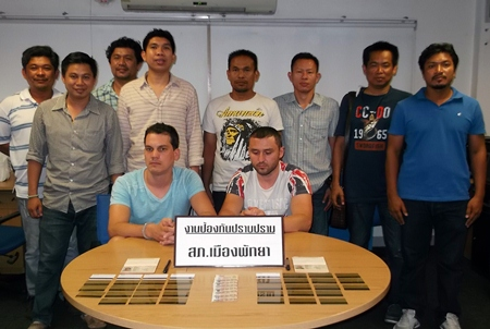 Police gather around the two Bulgarian suspects apprehended for allegedly using fake ATM cards to loot bank machines in Pattaya.