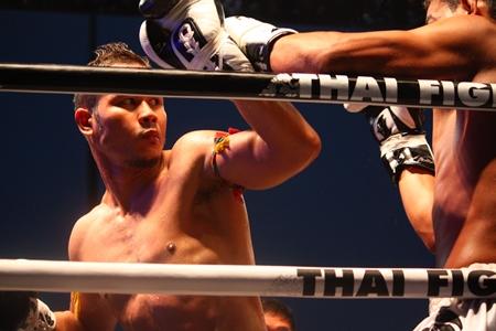 Yodsonklai Fairtex (left) blocks a punch from Uzbekistan's Naimjon Tuhtobaev.