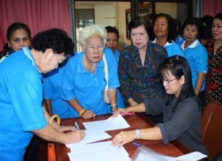 Members of Pattaya's Elderly Club sign up for a city-organized meditation and merit-making trip to Issan.