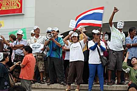 """About 200 anti-government protesters - many wearing white masks - converge on the Tesco-Lotus North Pattaya branch.  The group's Facebook page says it represents """"people power"""" urging peaceful opposition to """"parliamentary monopoly and corruption."""""""