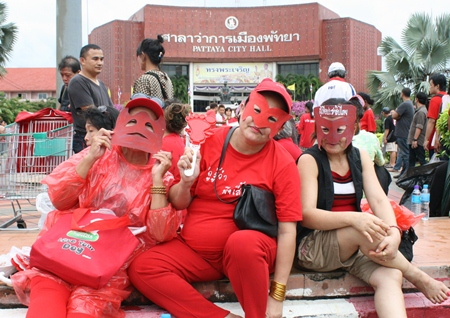 """Some red shirted followers of the UDD wore their own masks, whilst others shouted down the """"V for Thailand"""" across the street."""