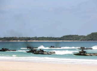Combined forces storm the beaches in Sattahip in amphibious vehicles during the 2013 CARAT military exercises.