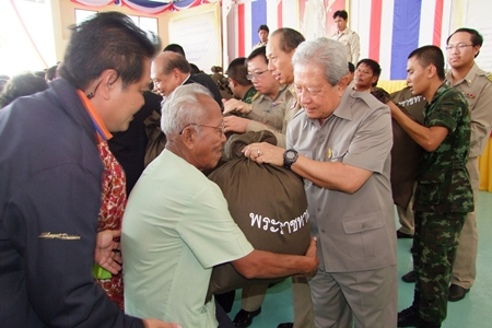 Privy Councilor Gen. Surayud Chulanont, representing the Their Majesties the King and Queen, presents aid bags to Koh Si Chang residents in need.