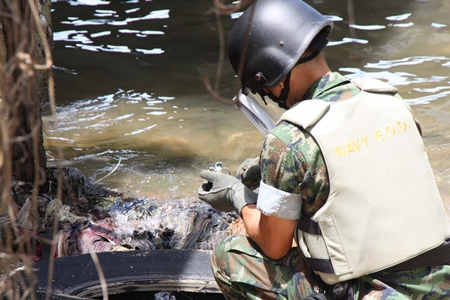 A Naval Ordinance Department bomb squad officer is able to remove the device without it detonating.
