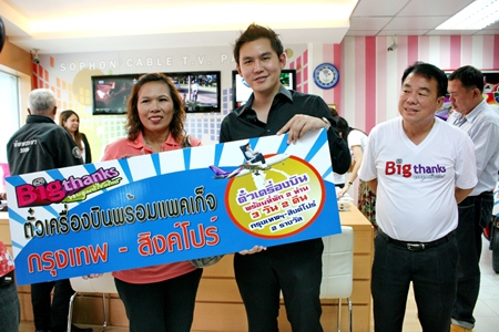 Mrs. Lamyai Thupwan (left) accepts the award from Rattakit Hengtrakul, deputy MD of Sophon Cable TV Pattaya, winning tickets from Bangkok to Singapore for 3 days and 2 nights.