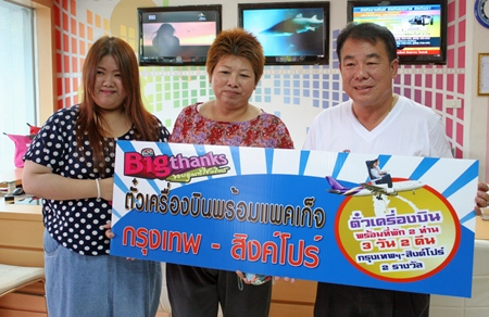 Malee Panchai (2nd left), the second lucky winner who won air tickets from Bangkok to Singapore for 3 days and 2 nights, receives her prize from Suwat Rachotwattanakul (right), deputy MD of Sophon Cable TV Pattaya.