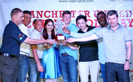 Team Etihad players Khun Phakorn, Khun Payunsak, Lee Sharpe and Russell Jay Darrell stand on stage with the winner's trophy alongside Dennis Irwin, Clayton Blackmore and Andy Cole.