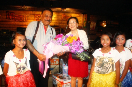Aunty Toy (right) and children from the CPDC center present flowers to Peter.