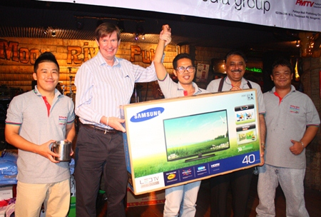 """Thepporn Donvithai (center) from the accounting department wins the night's grand prize, a 40"""" flat screen TV donated by Jan Olav Aamlid (2nd left)."""