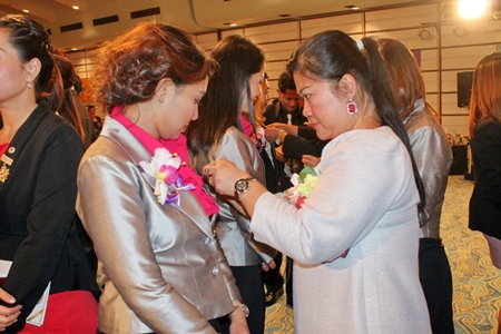 Members pin brooches on new 30 members during the candle lighting ceremony.