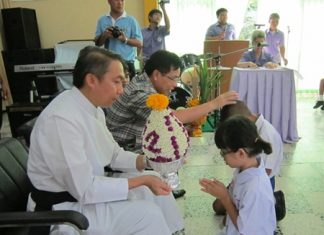 Students from nursery present flowers, candles, and incense to Father Pattarapong Srivorakul, president of Father Ray's foundation (left), and Chonburi Primary Education Region 3 Deputy Director Supamit Sirakantamakul.