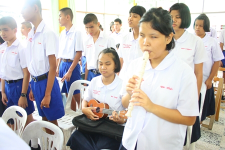 Students singing and playing instruments for the song 'Amazing Grace'.