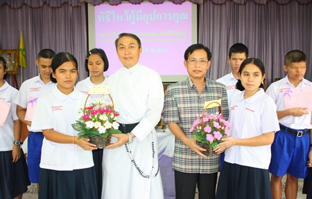 Student representatives from the Redemptorist School for the Blind present hand-made flowers to thank Father Pattarapong Srivorakul and Supamit Sirakantamakul.
