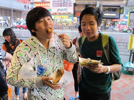 This tastes good! A Year 9 student samples some Hong Kong food.