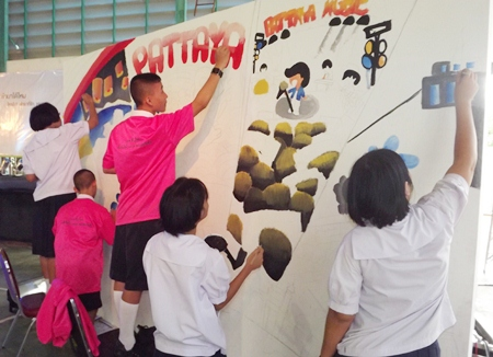 Students painting on the 'white wall'.