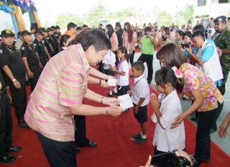 Deputy Gov. Pornchai Kwansakul, along with other Chonburi officials, hand out scholarships for area children.