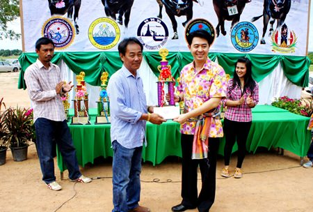Chonburi MP Poramet Ngampichet (right) presents the winning trophy and 5,000 baht to Sheriff Suwit (left), owner of Buffalo no. 1 that won the Special Junior category.