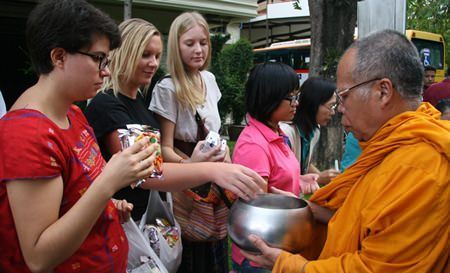 Foreign volunteers give alms to the monks.