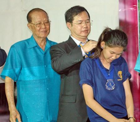 Father Picharn Jaiseri removes the president's sash from outgoing president Suchakorn Krajangjit.