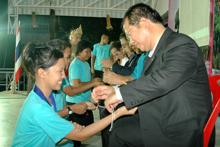 Rotary leaders tie sai-sin around the wrists of the Banglamung School Interact Club's new committee.