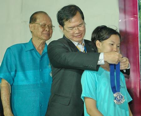 Father Picharn Jaiseri presents the president's sash to new president Lalita Phetphuang.