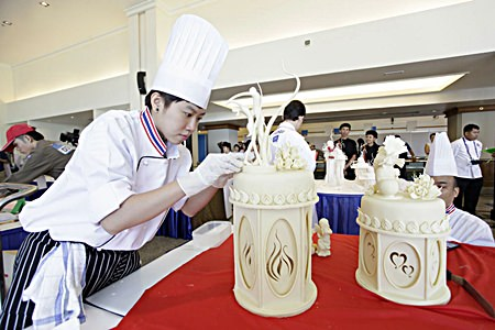 This chef is concentrating hard whilst decorating a cake in the Wedding Cake decoration contest.
