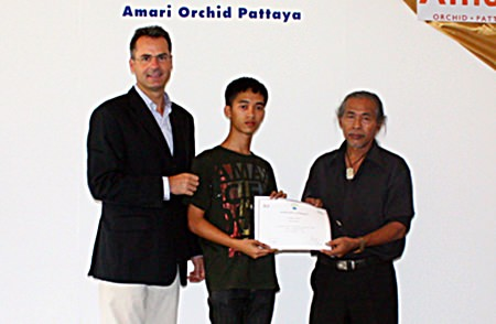 Richard Margo (left), Resident Manager of the Amari Orchid Pattaya, and Chanarong Kosolwat (right), free artists, present a certificate to Nattawut Chumanowat (center) from Silapakorn University.