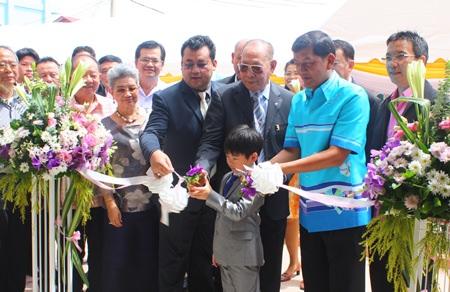 Chao Jiramongkol (center) and family, along with Chonburi Permanent Secretary Chaowalit Saeng-Uthai (2nd from right), cut the ribbon to open the new Chao Jiramongkol building at Banglamung Hospital.