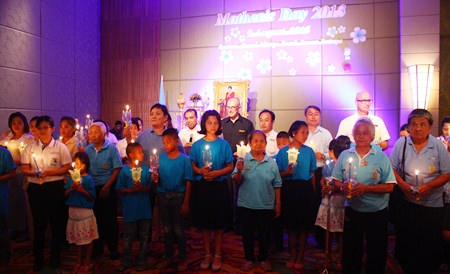 Centara Grand Mirage Beach Resort Pattaya GM Robert John Lohrmann (back row, center) leads employees, administrators, elders from Banglamung Elderly Center and children from Father Ray Children's Village to light the candles in honor of HM the Queen on her 81st birthday.