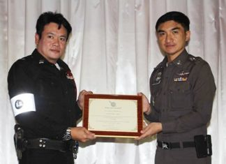 Pattaya Superintendent Col. Suwan Cheaonawinthawat presents a citation to Sen. Sgt. Maj. Jinna Son-unn, a traffic officer cited for ethical and moral behavior.