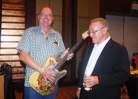 (L to R) Richard Kings holding his new replica of Jimmy Page's Dragon Telecaster guitar alongside him is Niven Walters who crafted and donated it.
