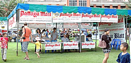 Staff from Pattaya Mail Publishing Co. Ltd., a sponsor since the first charity drive, hand out free newspapers at the fair.