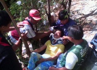 Rescue workers tend to Chiew Juayee, a Chinese tourist who fell from an observation point on Pratamnak Hill.