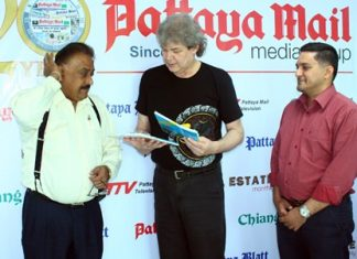 "Pattaya Mail Media Group Managing Director Pratheep ""Peter"" Malhotra (left) and General Manager Kamolthep ""Prince"" Malhotra (right) present Hucky with commemorative books honoring HM the King of Thailand. Hucky has transposed many of His Majesty's musical compositions for the guitar."