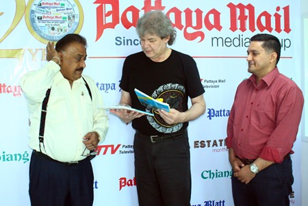 """Pattaya Mail Media Group Managing Director Pratheep """"Peter"""" Malhotra (left) and General Manager Kamolthep """"Prince"""" Malhotra (right) present Hucky with commemorative books honoring HM the King of Thailand.  Hucky has transposed many of His Majesty's musical compositions for the guitar."""