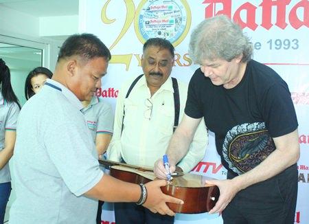 "Hucky autographs a guitar for head graphics man, Thanawat ""King"" Suansuk."
