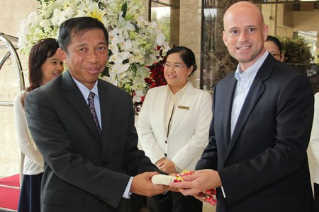 Dominique Ronge (right), general manager of Centara Grand Phratamnak Pattaya presents a hand garland to Admiral Taweewuth Pongsapipatt (left), Chief of Staff, Royal Thai Navy on his arrival to stay as the first guest at the newly opened resort.