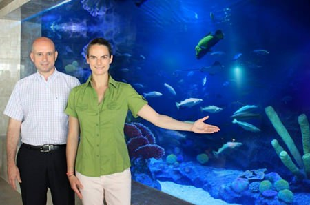 Dominique Ronge (left) stands with the hotel's professional aquarium specialist Patricia Campos Salaberri next to one of the main lobby aquariums that holds exotic marine species, including black tip sharks and groupers.